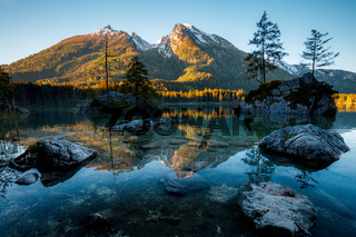 Fantastic sunrise at Hintersee lake. Beautiful scene of trees on a rock island during Spring