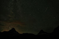 Logan Pass in the night with starry sky and the light of a forest fire in the background, Glacier National Park, Montana, USA
