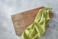 A wooden board with a green kitchen napkin on a gray concrete background with a copy space. Top view