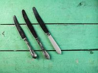 Vintage kitchen knives on a painted wooden