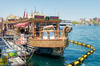 Traditional fast food bobbing boat serving fish sandwiches at Eminonu with chefs preparing meals, Istanbul, Turkey