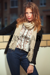 Young fashion girl in black cardigan and scarf in city street
