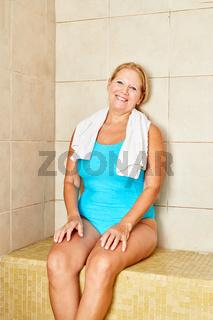 Senior Frau sitzt in einem gefliesten Bad