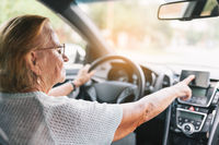 Elderly woman behind the steering wheel of a car using her satnav