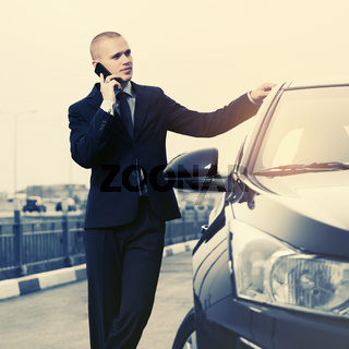 Young businessman in dark blue suit calling on cell phone next to his car