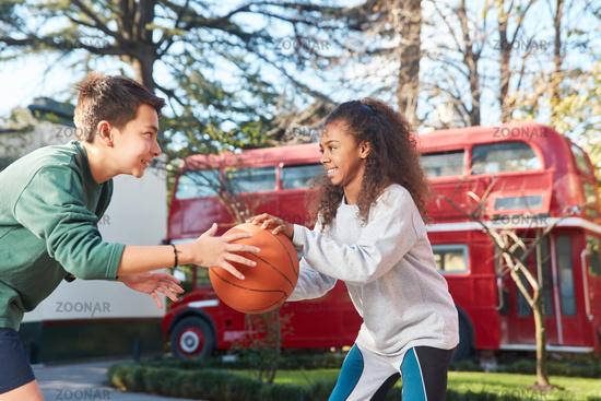 Teenager spielen zusammen Basketball