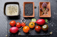Top view at fresh organic vegetables on slate stone tray with spices and sauces aside closeup dark concept photo