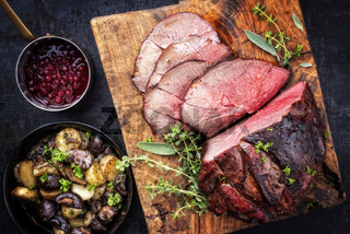 Barbecue dry aged haunch of venison with mushroom and potatoes as close-up on an old cutting board