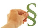 Hand hält grünes Paragraph Symbol