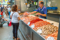 Seller shows fresh shrimp to buyer in the central market in Malaga, Spain.