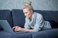 Happy blond woman lying prone on sofa and working on laptop computer