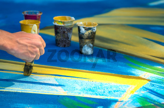 Street art. Drawing on an artistic scene in the city. Female hand with brush for drawing.