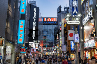 TOKYO, JAPAN - 12 FEB 2018: People walking in the street in Shibuya surrounded by buildings and bright colorful billboards