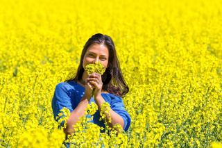 Woman smelling yellow flowers in rapeseed field