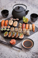 Assortment of different kinds of sushi rolls placed on black stone board
