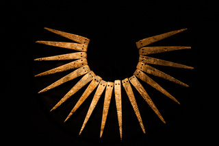 Ancient Inca necklace in black background.