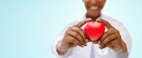 african american doctor hands holding red heart