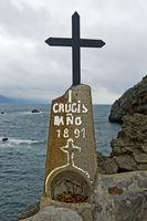 Schwarzes Metallkreuz auf einem Felsblock über der Bucht von Biskaya, Insel San Juan de Gaztelugatxe
