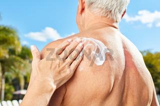 Frau reibt Sonnencreme auf Rücken