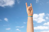 hand with gay pride rainbow wristband shows rock