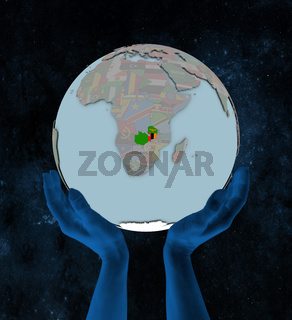 Zambia on political globe in hands