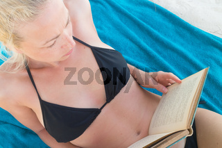 Beautiful girl lying at the beach in her swimsuit and reading a book