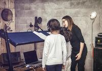Children with music or acting teacher in recording studio