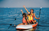 Mother with two daughters stand up on a paddle board