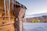 Icicles on the roof of wooden hut