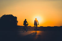 silhouette of two people riding bicycle with sunset sky background