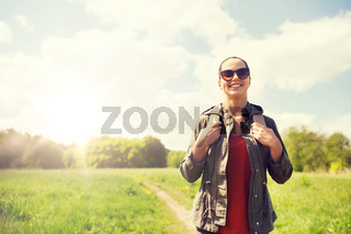 happy young woman with backpack hiking outdoors