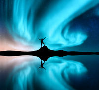 Northern lights and silhouette of a man with raised up arms