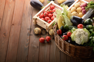 Basket of Organic Vegetable Food Ingredients and crates of potatoes and tomatoes on wood background