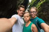 Selfie of family on the waterfall background