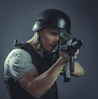 Security, paintball sport player wearing protective helmet aiming pistol ,black armor and machine gun over blue chroma background