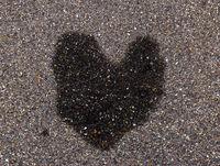 Herzförminger Wasserfleck auf asphaltiertem Gehsteig