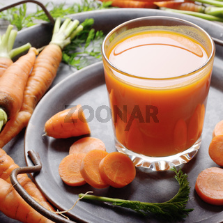 Vegetarian background of old fashioned tray with fresh organic carrots and juice on kitchen wooden table