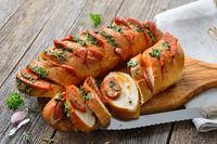 Überbackenes Kräuterbaguette mit Salami