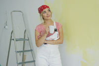 Smiling woman painter standing with drink