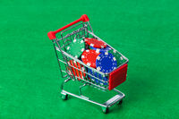 Casino chips in shopping cart on green table