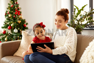 mother and daughter with tablet pc on christmas