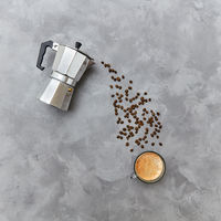 Aromatic coffee beans in the form of a pouring drink from italian metal coffee maker on a gray background with copy space. Flat lay