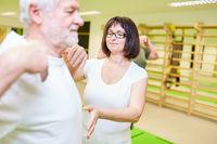 Physiotherapeutin betreut Senior bei einer Rückenübung