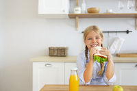 Happy little girl enjoying healthy breakfast eating sandwich and fruits and drinking orange juice sitting at bright sunny kitchen
