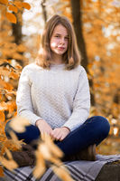 Teenage girl sitting in autumn garden