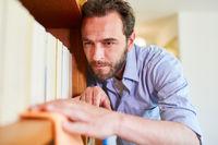 Hausmann beim Staub wischen reinigt Bücherregal
