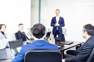 Colleague asking question to business team leader.
