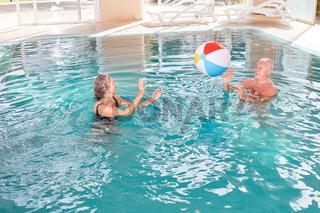Senioren Paar spielt mit einem Ball im Pool