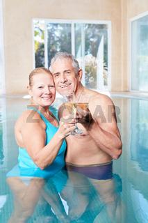 Paar Senioren feiert mit Sekt im Pool