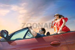 happy friends driving in convertible car over sky